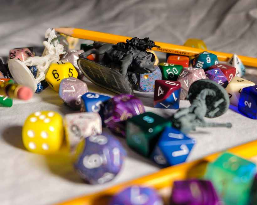 A pile of dice, pencils, and figurines used for a tabletop role-playing game.