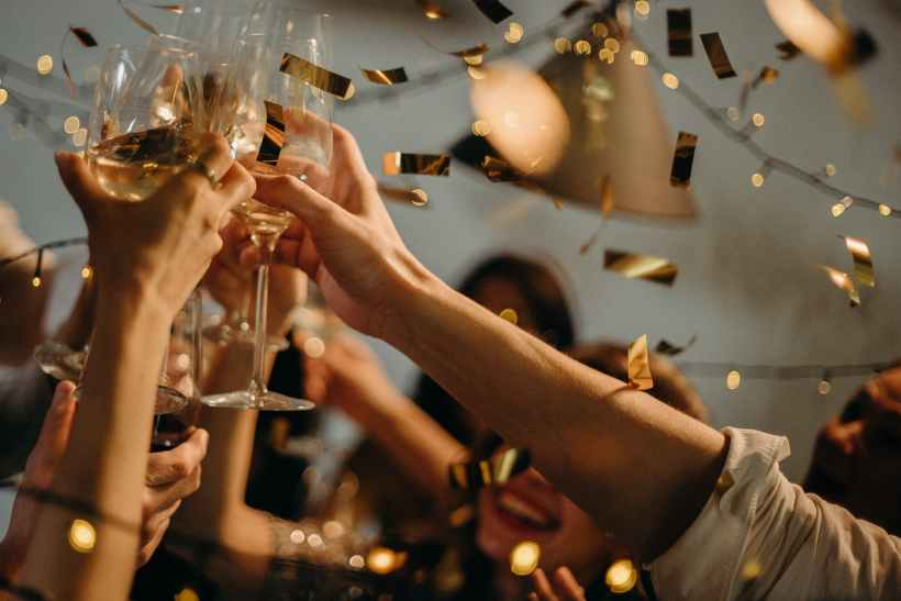 Hands holding champagne glasses and toasting.