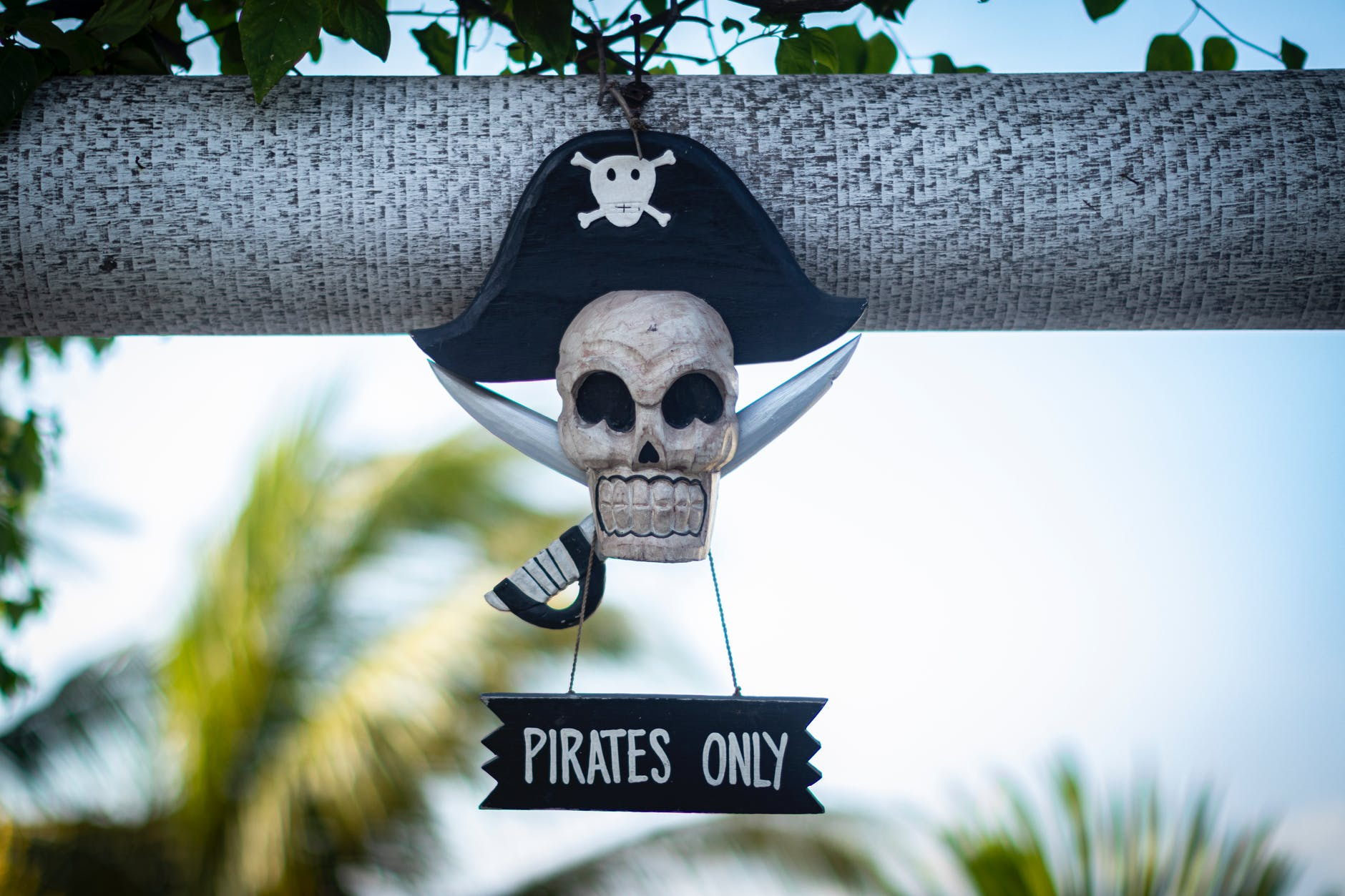 """A decoration shaped like a skull in a pirate hat and crossed swords, with a sign that reads """"Pirates Only""""."""