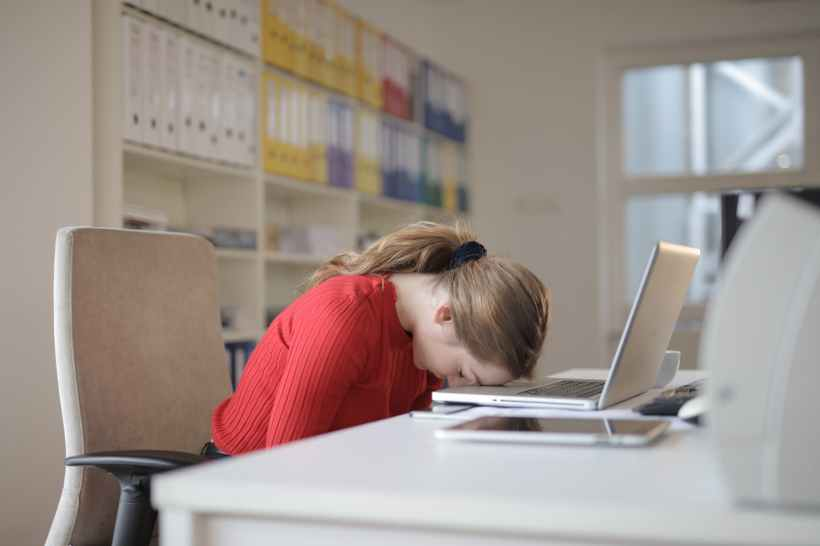 A tired woman slumped over her computer in exhaustion.