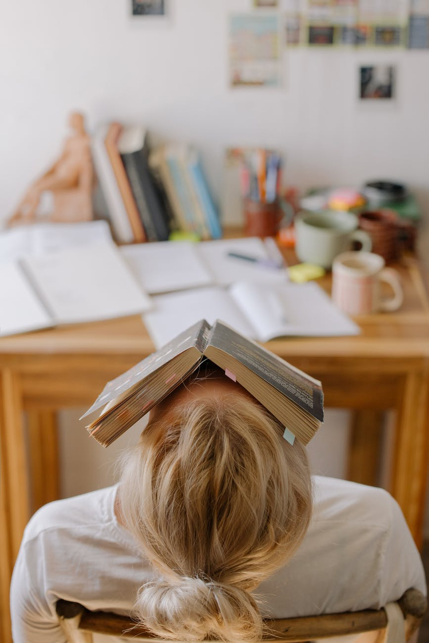 A woman, slumping back in exhaustion, with a book covering her face.