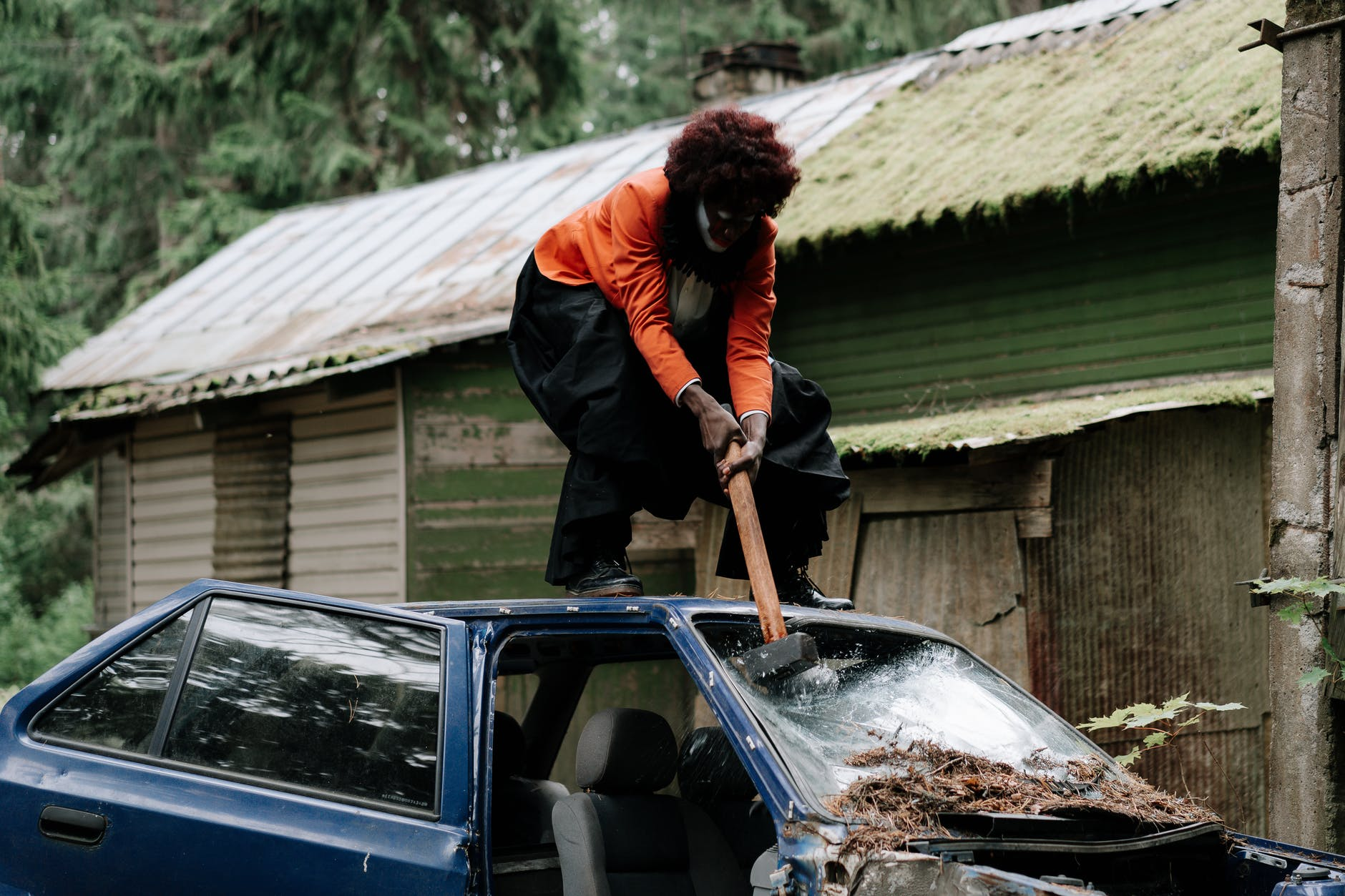 A woman smashing a car's windshield with a sledgehammer.