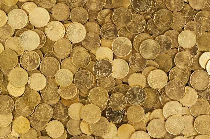 Many gold coins spread across the ground. Photo by Pixabay on www.pexels.com