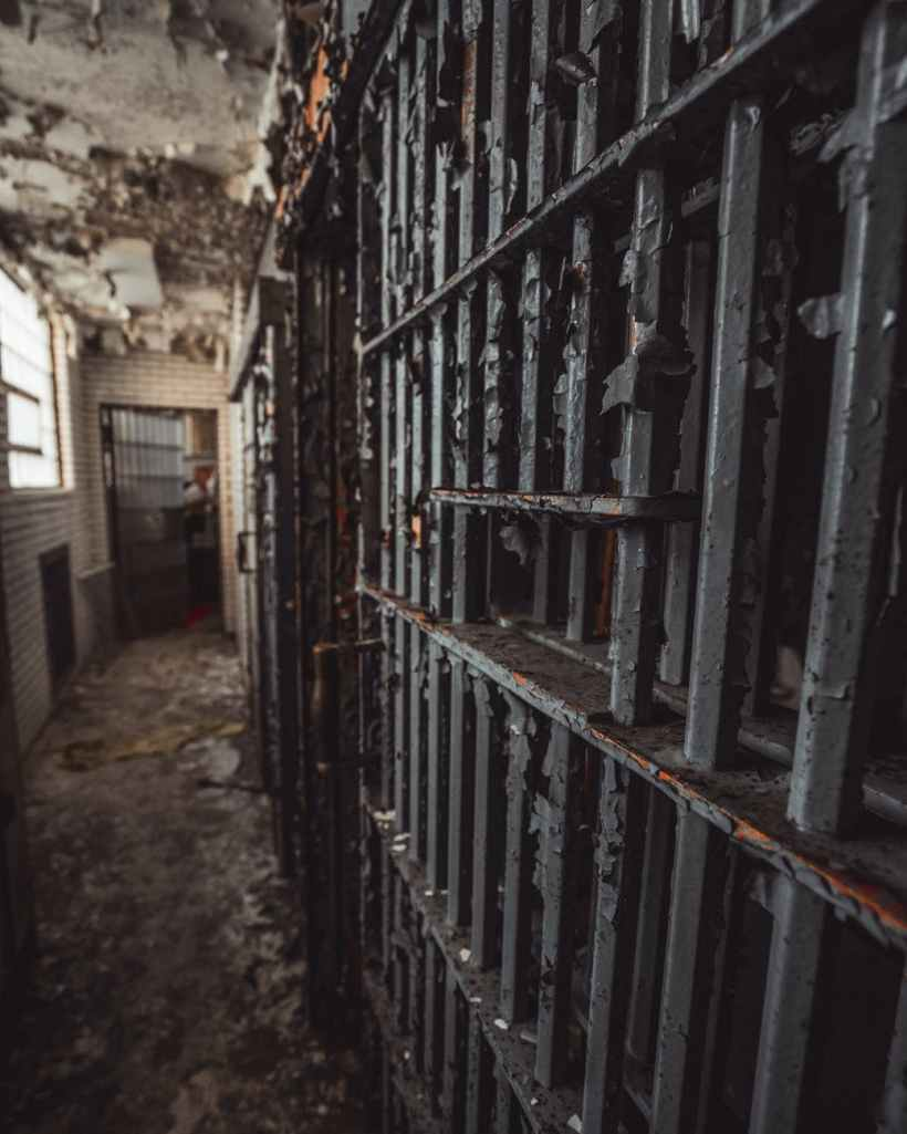 The iron bars of a prison cell in an old hallway. Photo by Cameron Casey on www.pexels.com