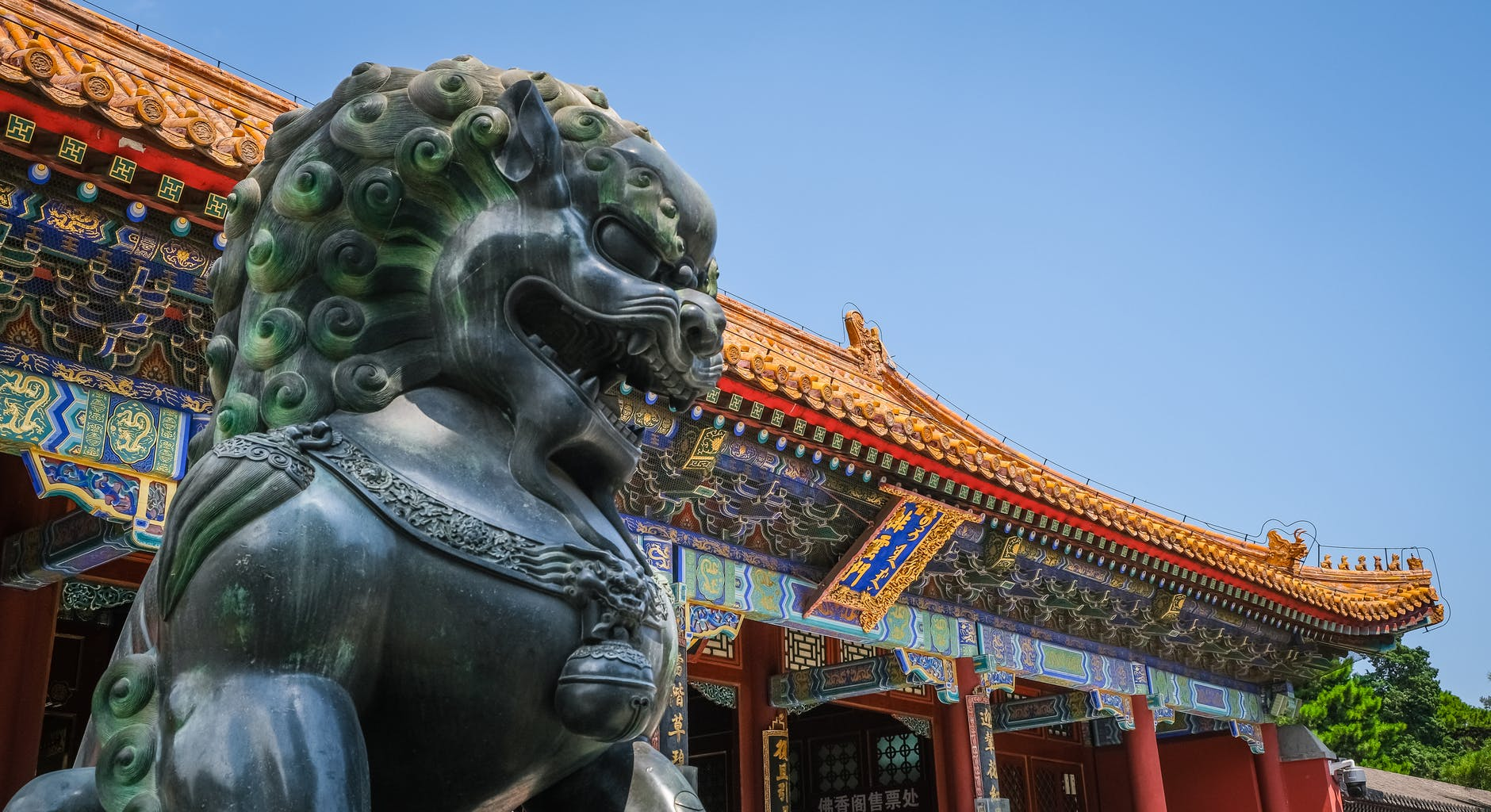 The exterior of a Chinese building, and the Stone Lion statue outside it.