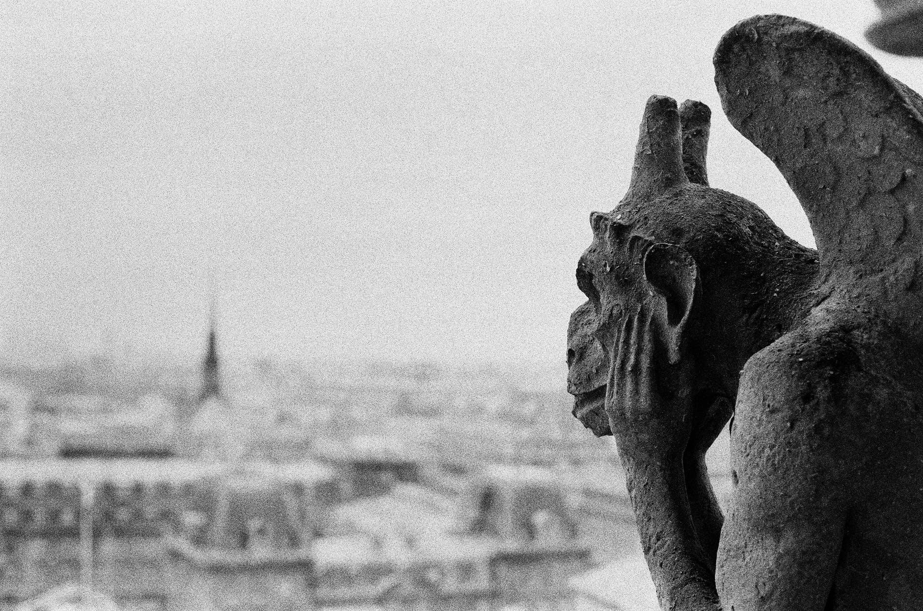A gargoyle at Notre-Dame de Paris overlooking the Paris skyline.