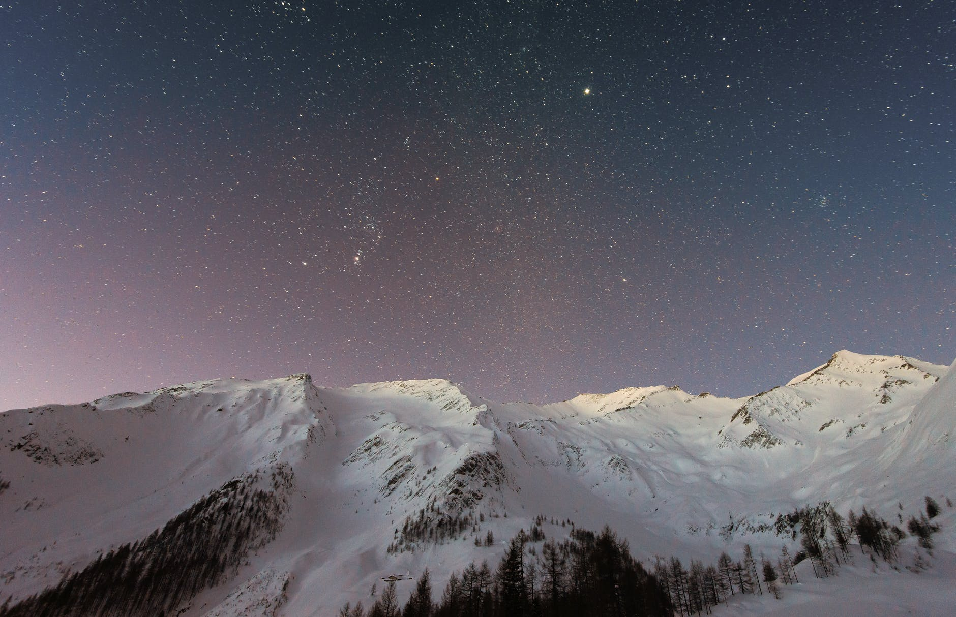 A sky full of stars above some snowy mountains. Photo by eberhard grossgasteiger on pexels.com