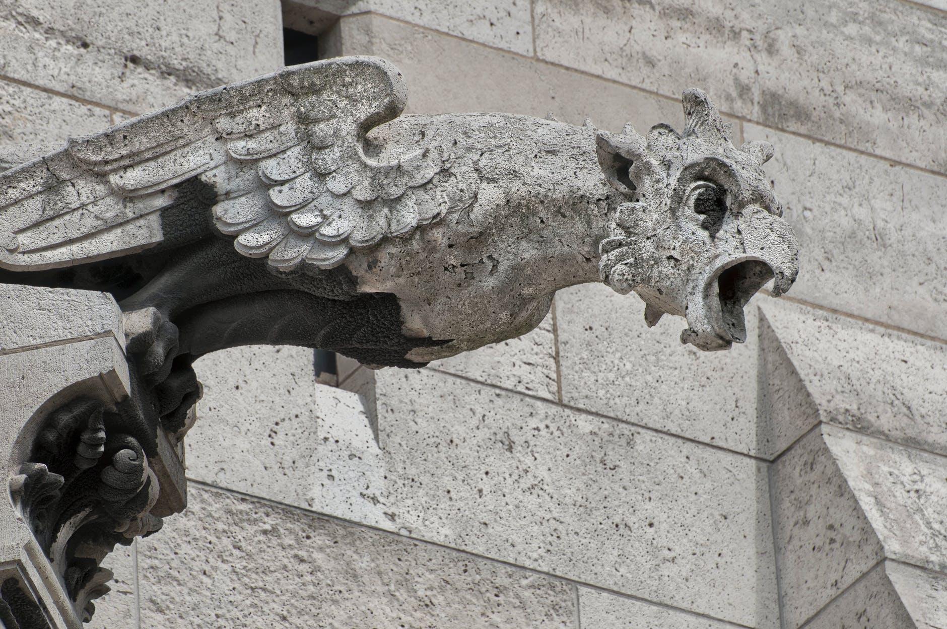 A birdlike gargoyle on an old building.