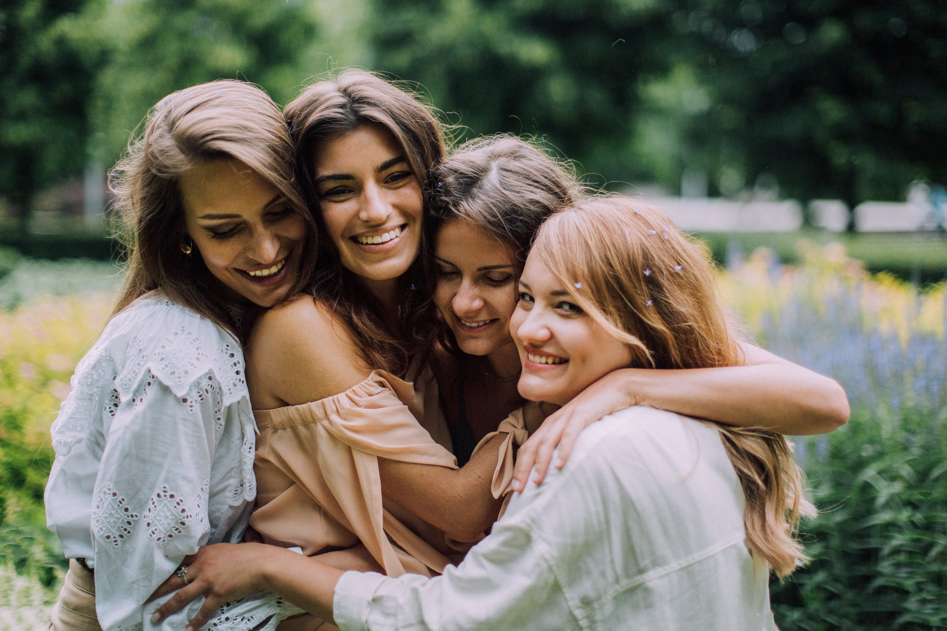 Four women in a group hug.