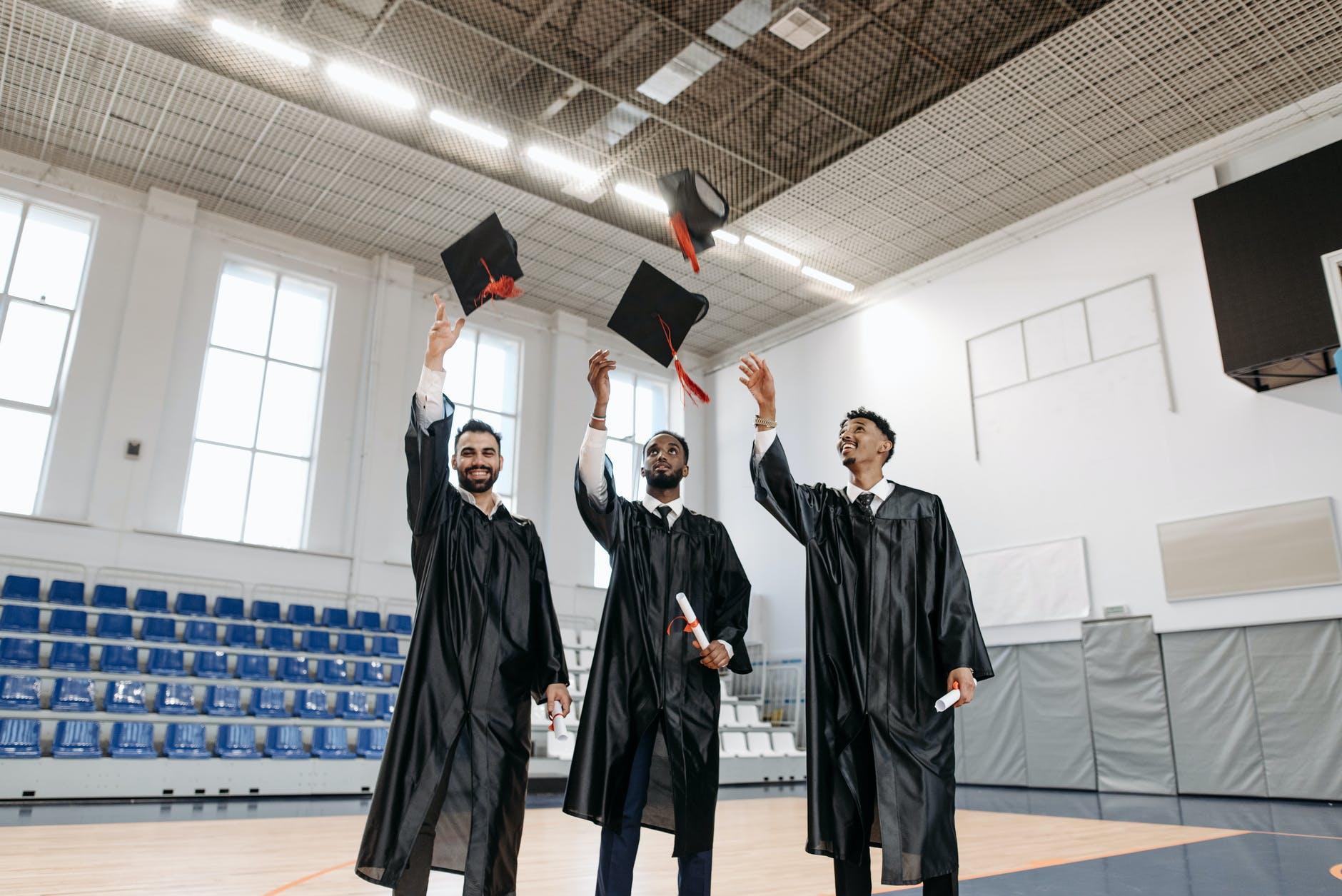 Three men in a school gymnasium celebrating their graduation.