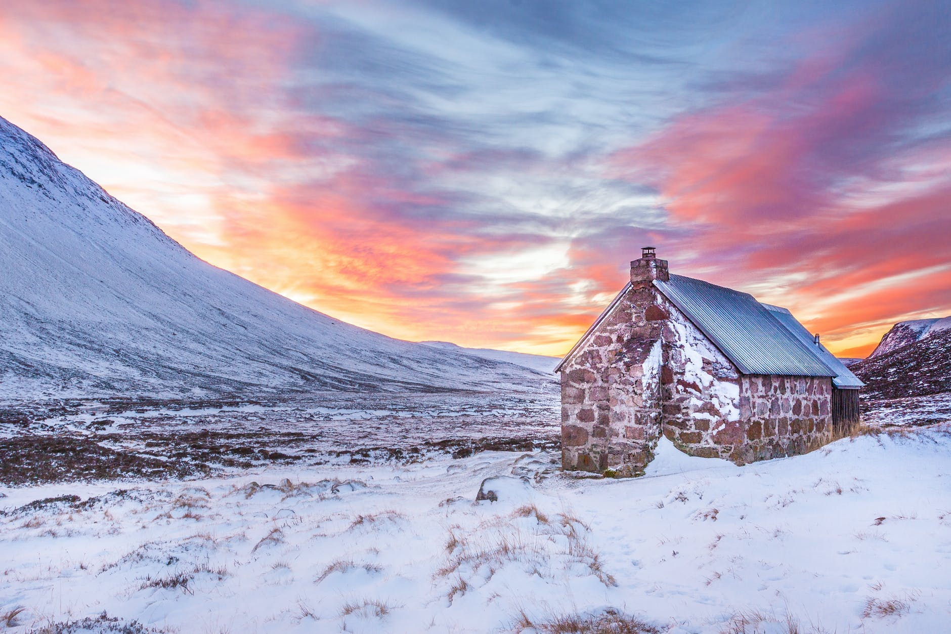 A cottage in a snowy landscape at sunset.
