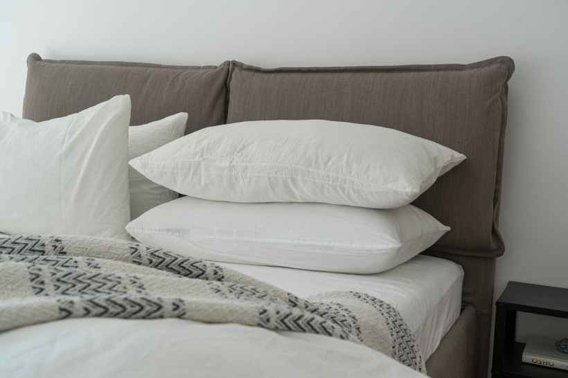 Several pillows laid out on a bed.